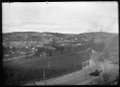 View of The Glen, South Dunedin, with a train crossing the railway overpass above South Road. ATLIB 274010.png