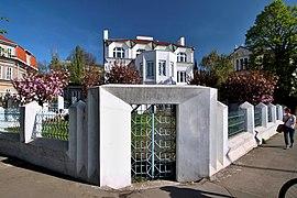 Vue du portail piétonnier et du muret d'enceinte d'une villa, aux formes anguleuses, le tout dans des tons blancs