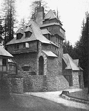 A monochrome photograph of a 75-foot-tall multi-room building with castle-like features, made of river rock, with many steeply pitched roof elements.
