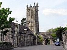 Une église de pierre grise au clocher rectangulaire.