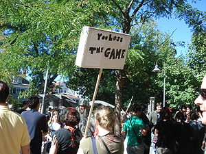 "The Game (mind game) - A girl holds up a sign reading ""You Lose The Game""."