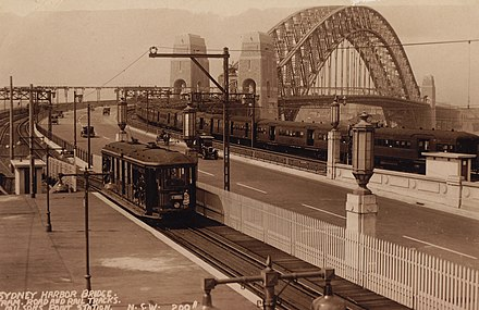 A tram and a train arrive at Milsons Point station 09 - Milsons Point Station (6433345329).jpg