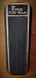 "A color image of a 1968 King Vox Wah pedal. The foot pedal is black with chrome accents and has a ""King Vox Wah"" label on the top."