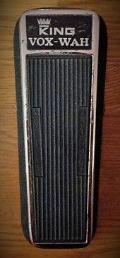 """Una imagen en color de un rey Vox Wah pedal de 1968.  El pedal es de color negro con detalles en cromo y tiene una etiqueta """"Rey Vox Wah"""" en la parte superior."""