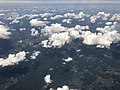 2019-07-19 13 07 55 Cumulus clouds developing over the north end of Massanutten Mountain along the border of Shenandoah and Warren Counties in Virginia, viewed from an airplane which recently took off from Washington Dulles International Airport.jpg
