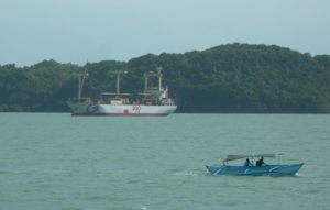 Iloilo Strait - A cargo ship of 2GO Freight in the Iloilo Strait, with a pumpboat and Guimaras Island in the background.