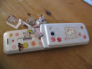 A Japanese cell phone with various stickers an...