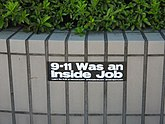 "A photo of a black, rectangular sticker that falsely claims that ""9/11 was an inside job"" in big white text, under the big text was a suggestion to go to three conspiracy theory sites."