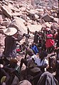 ASC Leiden - W.E.A. van Beek Collection - Dogon daily life 23 - Yèngulu Yangau (with hat) addresses the young people from neighboring Amani visiting the market in Tireli, Mali 1985.jpg