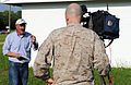 A U.S. Marine operates the camera as Art Kohn, background, a news reporter with WAVY TV 10, gives a news report about U.S. Service members assigned to Joint Task Force Civil Support during exercise Sudden 130521-F-QH128-718.jpg