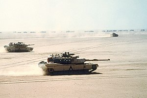 M1 Abrams - Abrams tanks move out on a mission during Desert Storm in 1991. A Bradley IFV and logistics convoy can be seen in the background.