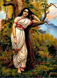 A painting of a young fair woman clad in a white sari with a red border stands, leaning on a tree, as she moves her left hand through her long black hair and holds a flower basket in her outstretched right hand.