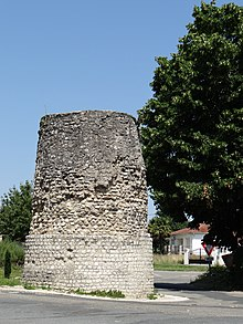 Photograph of an isolated stone tower in a modern setting