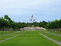 Travnaté pole vedoucí k terasovité stránce s pěti vlajkami