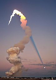 Shuttle launch of Atlantis at sunset in 2001. The sun is behind the camera, and the plume's shadow intersects the moon across the sky.
