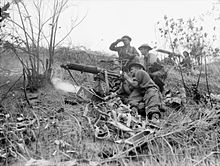 Soldiers firing a medium machine from the slope of a hill