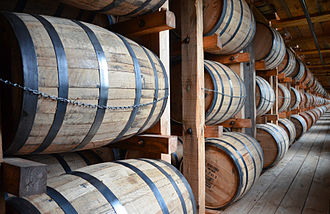 Bourbon whiskey - American white oak barrels filled with new bourbon whiskey rest in a rack house, giving bourbon its well-known copper color