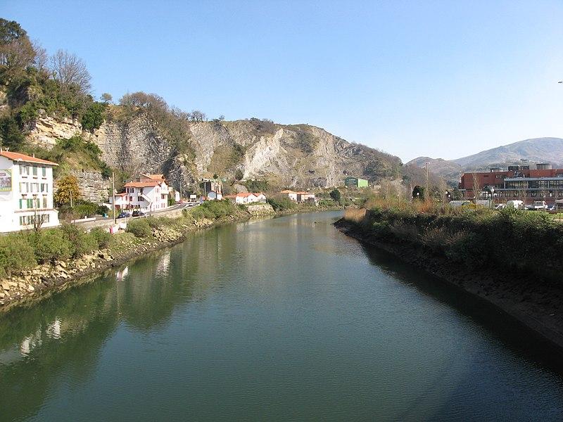La Bidassoa, vue vers l'est et vers l'amont depuis le pont de Béhobie. Le pont de Béhobie est à cheval entre la commune française d'Urrugne (Pyrénées-Atlantiques, ouest des Pyrénées), et celle d'Irun en territoire espagnol. Irun possède donc la rive gauche vue ici - celle sur la droite de la photo, puisque nous regardons vers l'amont. Mais seulement environ 90 m de rivière longent le territoire d'Urrugne, dont environ 20 m en amont du pont (devant nous) et 70 m en aval du même pont (derrière nous). Toute la berge en rive droite vue ici (sur le côté gauche de la photo), y compris la première maison vue partiellement à gauche de la photo, est donc sur le territoire de la commune française de Biriatou, qui jouxte la limite sud-ouest d'Urrugne. On ne voit aucune portion de la rivière sur le territoire d'Urrugne.