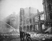 Firefighters battling against fire amongst ruined buildings