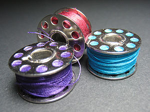 Three sewing machine bobbins with various colo...