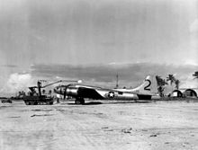 A propeller aircraft sits on a runway. A tracked vehicle with a crane lifts something above it. In the background are a jeep, three Quonset huts and palm trees.