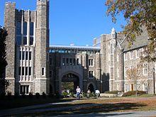 torre de cuatro pisos a la izquierda con un pasillo arqueado en el centro y peatones puente que conecta a la torre de tres pisos edificio gótico