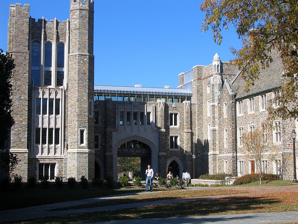 Four-story tower on left beset by arched walkway in center and pedestrian bridge connecting tower to three-story Gothic building