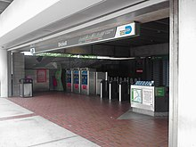 "The entrance to a metro station featuring a large number of turnstiles and a sign above that reads ""Brickell""."