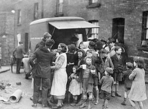 Swansea Blitz - Mothers and children in a working class area of Swansea have tea and sandwiches from a mobile canteen after a night's bombing.