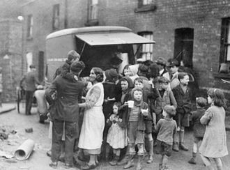 9th Anti-Aircraft Division (United Kingdom) - Mothers and children in a working class area of Swansea have tea and sandwiches from a mobile canteen after a night's bombing.
