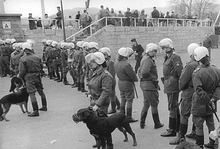 German police prepare for hooliganism by wearing riot gear and using police dogs. Bundesarchiv Bild 183-1990-0407-027, FC Carl Zeiss Jena - FC Berlin 1-1, Ausschreitungen.jpg