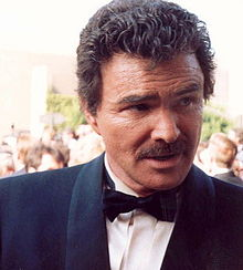 A middle-aged man, wearing a suit with a black bow tie.