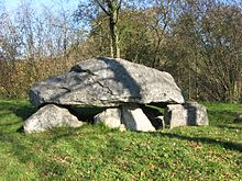 Photo d'un dolmen au centre d'une pelouse.