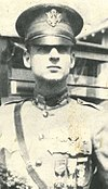 Head and shoulders of an officer in a neatly pressed military uniform with medals hanging from ribbons on his chest and a service cap.
