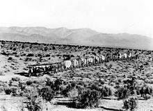 A train of over fifteen wagons crossing the desert, a flat sandy expanse with many scattered scrub-like bushes and a mountain range in the distance.