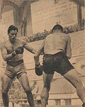 Deux boxeurs debout face à face devant une tribune pleine.