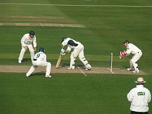 Fielding (cricket) - Example of two close fielders: a short leg and a silly point stand close to the batsmen on either side of the pitch. They are both wearing protective equipment (helmets and leg pads). The wicket keeper is 'standing up' to the stumps, and the square leg umpire is also visible.