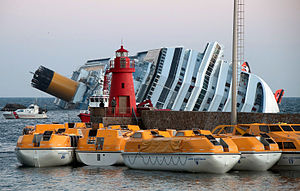 Costa Concordia disaster - Aground with rigid lifeboats in foreground and inflatables hanging from the side of the ship
