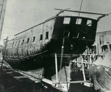 Photograph of a ship out of the water and partially disassembled