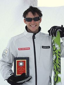 A man with brown hair, round head and wearing sunglasses is smiling broadly. He is wearing a white jacket and black gloves and is holding an award plaque in his right hand next to his midriff. His left hand is holding green-coloured skis.