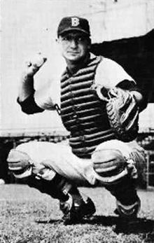A crouching man wearing a catcher's chestguard and baseball cap prepares to throw a baseball with his right hand