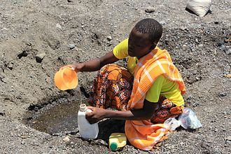 Stream bed - A woman digs in a dry stream bed in Kenya to find water during a drought.