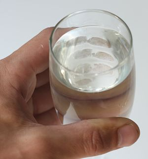 A hand holding a glass of water with fingerprints visible from the inside