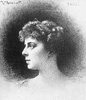 A woman's head and shoulders in profile looking to the left, with short, curled hair