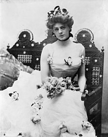 Ethel Barrymore, as a beautiful young woman, in a three-quarter length portrait, seated, facing front, wearing an elaborate gown and holding a bouquet of roses