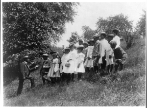 Outdoor education - Field trip: school children outdoors listening to man, c. 1899, US