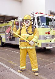 Firefighter in full turn out gear with a pickhead axe. This firefighter is dressed to demonstrate the gear; in reality the equipment would be adjusted.