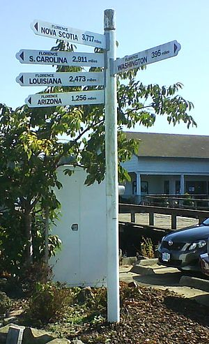 """Florence, Oregon - A sign in the Florence Old Town area denoting distances to other cities with the same city name """"Florence"""" in North America"""