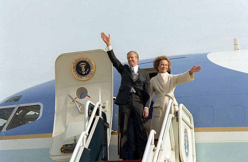 Former President and First Lady Carter wave from their aircraft.jpeg