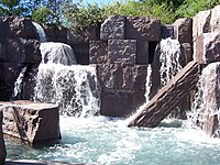 Waterfalls flowing over stone blocks into a pool